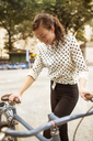 Woman holding bicycle while standing on road in central park - CAVF01717