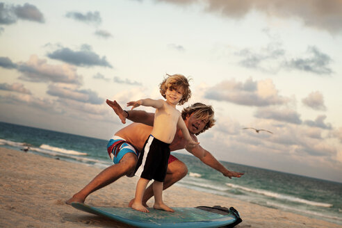 Portrait of father teaching son to surf at beach - CAVF01819