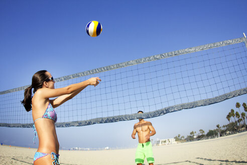 Couple playing beach volleyball against clear sky - CAVF01918