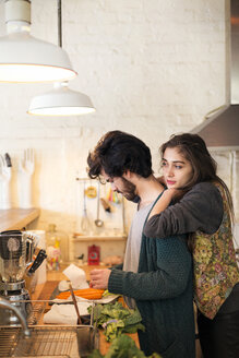 Woman leaning on man in kitchen - CAVF02059