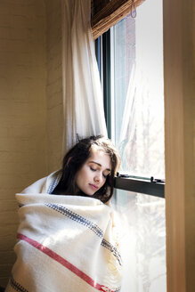 Woman with eyes closed while leaning on window at home - CAVF02071