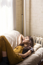 Woman looking up while relaxing on sofa at home - CAVF02074