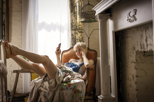 Woman using smart phone while reclining on chair at home - CAVF02080