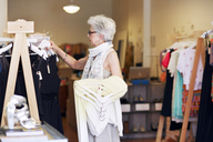 Side view of senior woman shopping in boutique store - CAVF02155