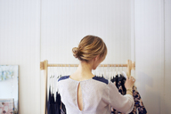 Rear view of woman arranging clothes in rack - CAVF02173