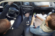 Overhead view of woman using smart phone while traveling with boyfriend in car - CAVF02182
