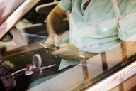 High angle view of man using smart phone while traveling in car seen through window - CAVF02233