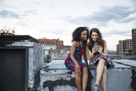 Friends using mobile phone while sitting on building terrace against sky - CAVF02251