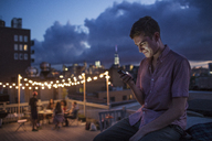 Man using mobile phone while sitting on building terrace at dusk - CAVF02254