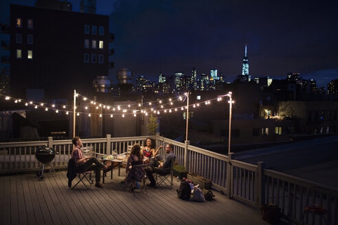 Friends enjoying on building terrace at night - CAVF02257