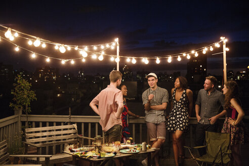 Friends talking while standing by railing on building terrace - CAVF02260