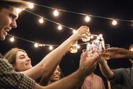 Low angle view of cheerful friends toasting drinks at party - CAVF02263