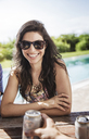 Cheerful woman in sunglasses sitting in backyard against sky - CAVF02269