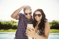 Happy couple taking selfie while standing against clear sky - CAVF02275