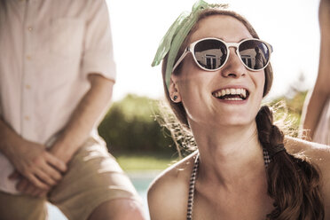 Happy woman in sunglasses at backyard on sunny day - CAVF02284