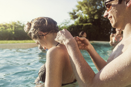 Happy man tying woman's bikini top while enjoying in pool - CAVF02293