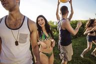 Cheerful friends enjoying in backyard on sunny day - CAVF02308
