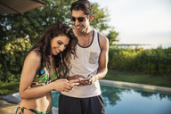 Cheerful couple using mobile phone while standing at poolside - CAVF02311