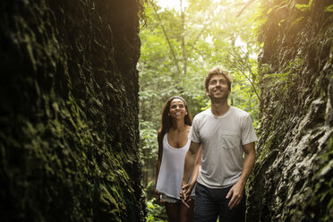 Couple looking up while walking in forest - CAVF02344