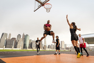 Athletes playing basketball in court against buildings - CAVF02353