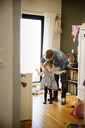 Father helping daughter in wearing dress at home - CAVF02404