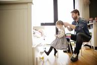 Man tying daughter's hair at home - CAVF02407