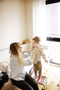 High angle view of mother changing daughter's dress at home - CAVF02419