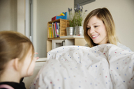 Happy mother looking at daughter in home - CAVF02422