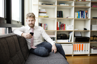 Man using mobile phone while sitting on sofa at home - CAVF02434