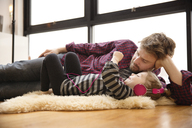 Girl listening music by father while lying on floor at home - CAVF02449