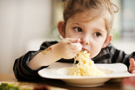 Girl looking away while eating noodles at table in home - CAVF02455