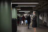 Side view of woman standing at subway station - CAVF02464