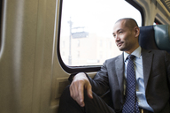 Businessman looking away while traveling in subway train - CAVF02467