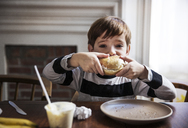 Portrait of boy eating hamburger at home - CAVF02545