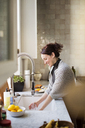 Side view of woman washing utensils at home - CAVF02557