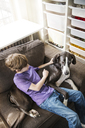 High angle view of boy sitting with dog on sofa at home - CAVF02599