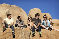 Low angle view of friends sitting on rock formation against clear sky - CAVF02755