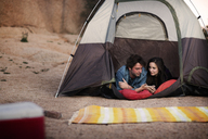 Couple talking while lying in tent - CAVF02761
