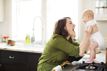 Happy mother playing with baby girl in bathroom - CAVF02839
