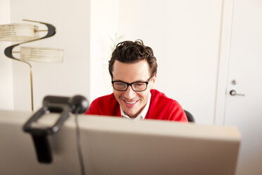 Smiling businessman looking at computer in office - CAVF02848
