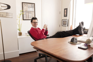 Portrait of smiling businessman relaxing in office - CAVF02851