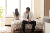 Couple sitting on bed after argument at home - CAVF02854