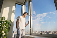 Low angle view of man looking though window at home - CAVF02869