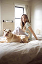 Portrait of happy woman with dog on bed - CAVF02884