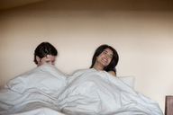 Cheerful couple relaxing under blanket on bed - CAVF02902