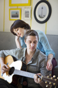 Woman listening to boyfriend playing guitar at home - CAVF02971