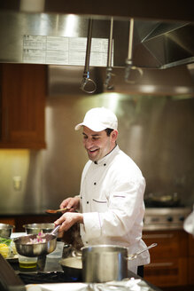 Happy chef cooking while standing at commercial kitchen - CAVF03028
