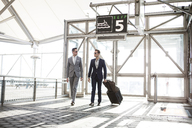 Businessmen with luggage walking in transportation building - CAVF03037