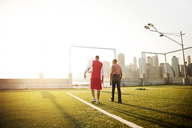Rear view of son and father walking on soccer field during sunny day - CAVF03148