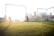 Father playing soccer with man on field during sunny day - CAVF03154